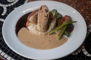 Roasted chicken Roulade Enhanced with red wine and orange liquor sauce and green black pepper sauce served with Mash Potato.